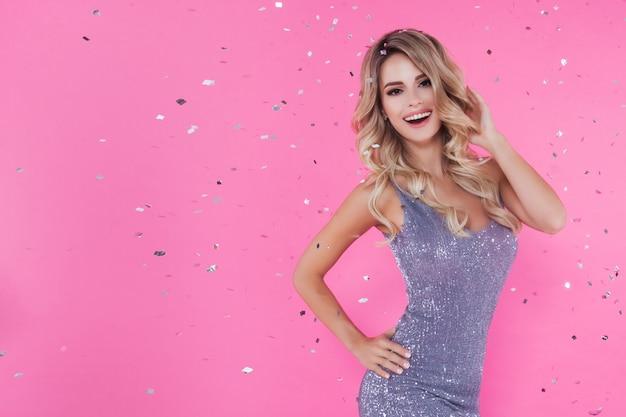 Красивая белокурая женщина празднует новый год или с днем рождения, бросая конфетти на розовый