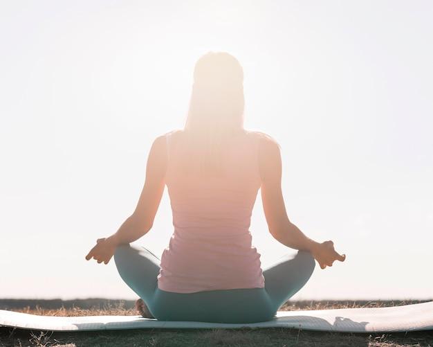 Bella donna bionda che fa yoga all'aperto