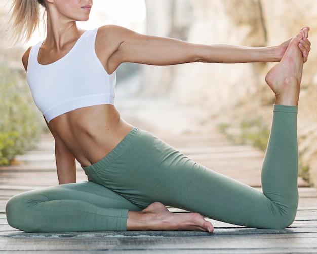 Beautiful blonde woman doing yoga outdoors