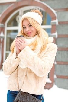 겨울 유행의 옷을 입고 거리에서 차를 마시는 아름다운 금발 여성