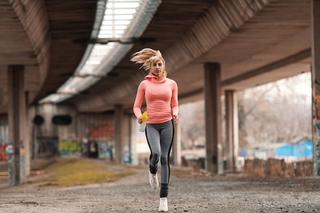Beautiful blonde woman dressed in sportswear running under the bridge and holding bottle with water.