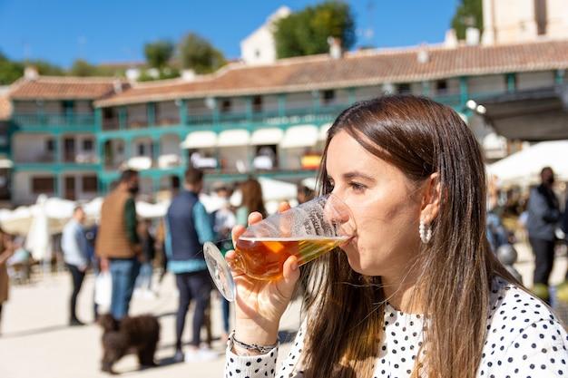 전형적인 마을 광장에서 맥주를 마시는 아름 다운 금발의여 인