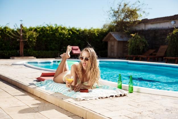 カクテルを飲んで、日光浴、スイミングプールのそばに横たわって美しいブロンドの女性