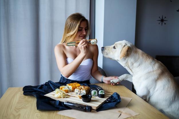 ラブラドール犬と一緒に寿司のクローズアップを食べる美しい金髪の女性、箸で巻き寿司を持って素敵なメイクで笑顔の女性。健康的な日本食。ダイエットコンセプト