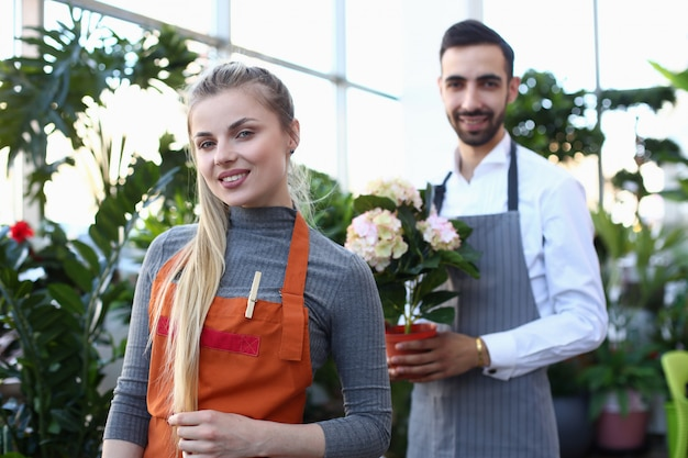 Beautiful blonde woman florist and man with flower. smiling girl gardener and male holding white blooming hydrangea in domestic plant center.