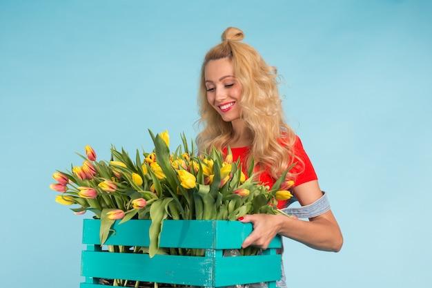 青い表面にチューリップとボックスを保持している美しいブロンドの女性の庭師