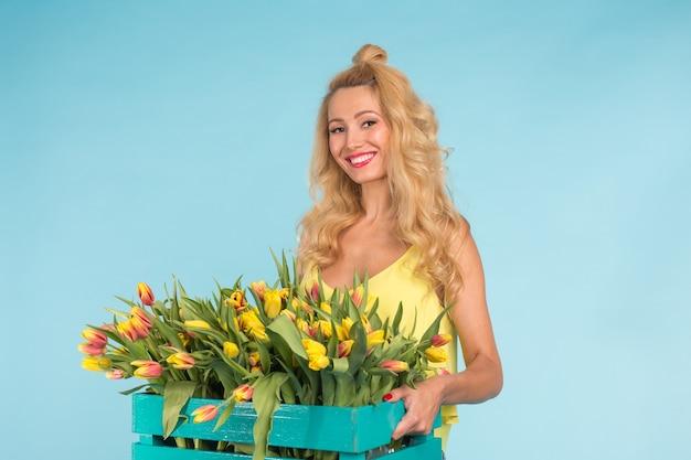 Красивая блондинка садовник держит коробку с тюльпанами на синем