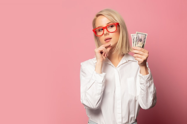 Beautiful blonde woman in glasses with dollars cash