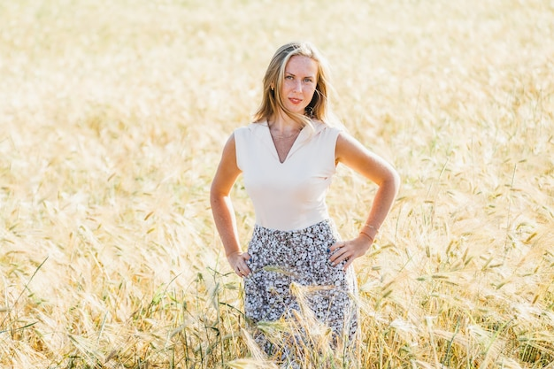 Beautiful blonde woman on a golden summer field