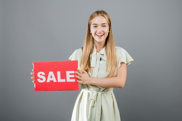 Beautiful blonde woman has sale sign isolated over grey