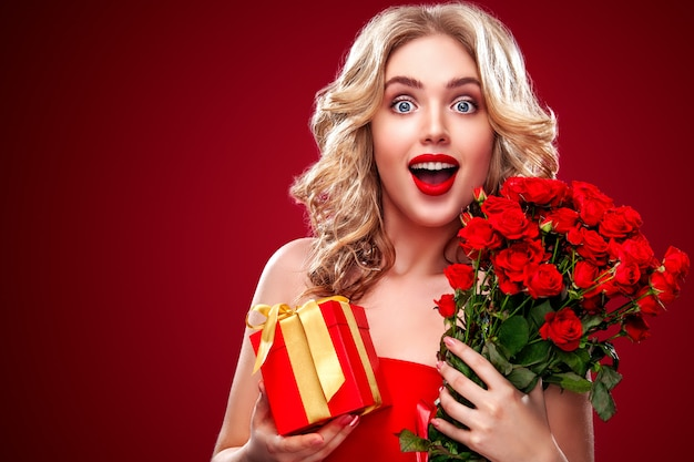 Beautiful blonde woman holding bouquet of red roses and gift