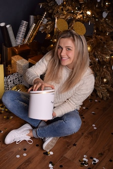 Beautiful blonde woman holding a box with a christmas present in her hands and smiling happily