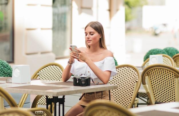 ストリートカフェのテーブルに座っている間彼女の手でスマートフォンを保持している美しいブロンドの女性