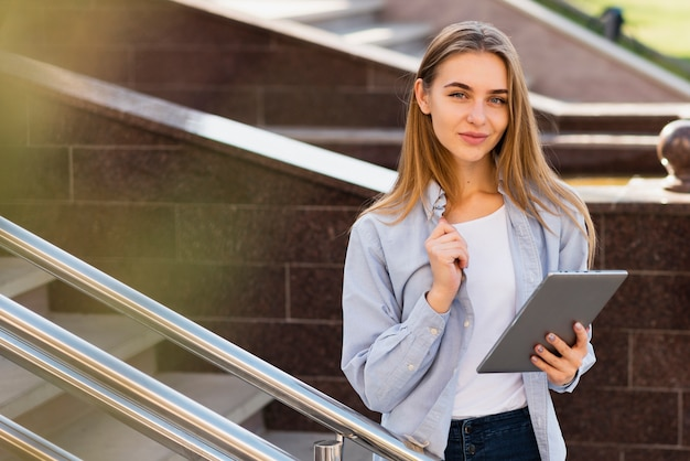 Beautiful blonde woman holding a tablet