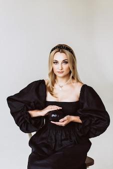 그녀의 손에 호박과 검은 리넨 드레스에 아름 다운 금발 여자. 에스닉 패션, 천연 직물. 할로윈 파티. 소프트 선택적 초점.