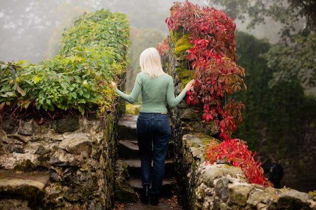 秋のバージニアクリーパーと庭の美しいブロンドの女性