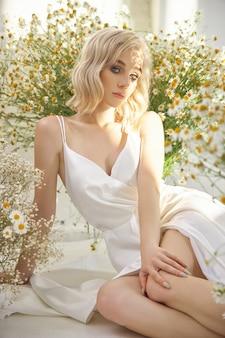 白いドレスを着た美しいブロンドの女性がカモミールの花の間で床に座っています
