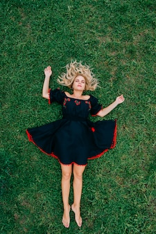 Красивая белокурая женщина в черном этническом льняном платье, лежащем на зеленой траве.