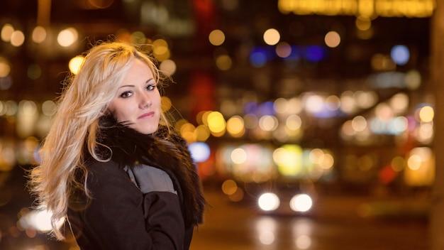 Красивая, белокурая женщина в автомобильных огнях в ночном городе.