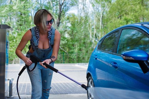デニムのオーバーオールを着た美しい金髪の女性が車を洗う