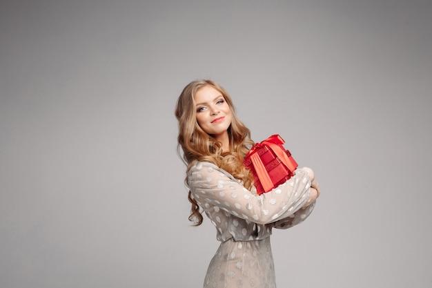 Красивая белокурая женщина в изящном платье и пятках со стеком подарков.