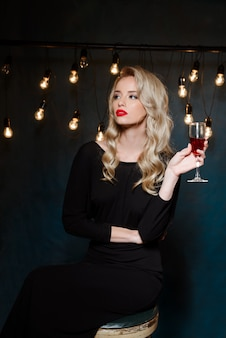 Красивая блондинка в вечернем платье позирует, держа бокал
