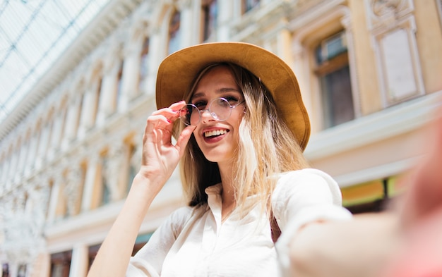 フェルトの帽子とメガネで美しいブロンドの女性
