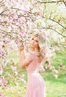Красивая блондинка в розовых цветах. весенний сад на солнце