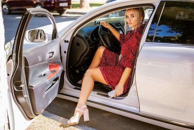 빨간 드레스에 아름 다운 금발의여자가 흰색 차에서 가져옵니다.