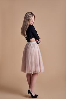 Красивая блондинка в юбке под направленным светом с тенью позирует на коричневом