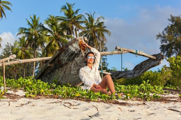 Красивая блондинка в вязаном белом купальнике сидит на одиноком пляже с бирюзовой водой и белым песком возле традиционного доу рыбацкой лодки. занзибар. нунгви.