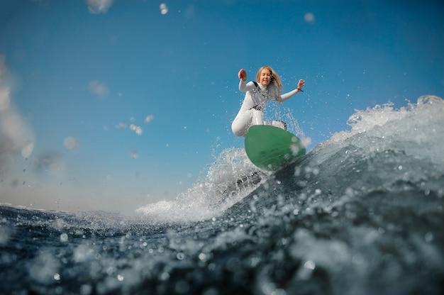 Красивая блондинка в белом спортивном купальнике катается на зеленом вейкборде на согнутых коленях