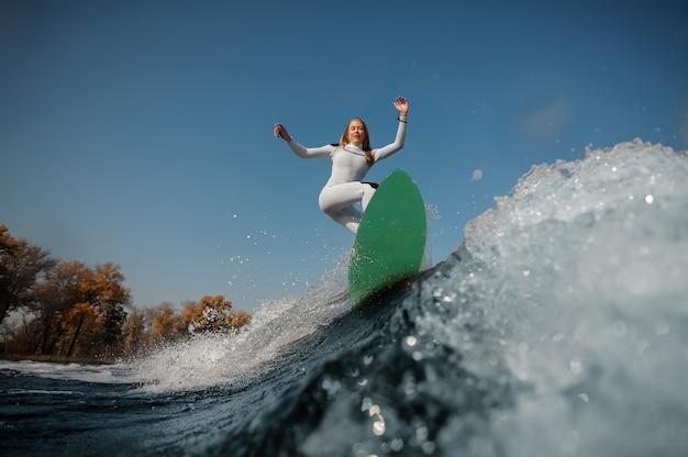 Красивая блондинка в белом купальнике катается на зеленом вейкборде на согнутых коленях