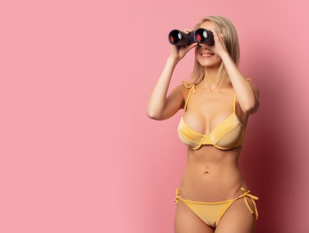 Красивая белокурая женщина в желтом бикини с биноклем