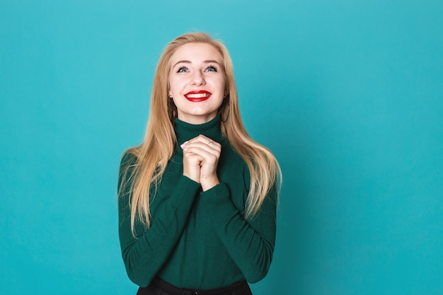 Beautiful blonde woman is grateful for something standing on a blue background wearing sweater