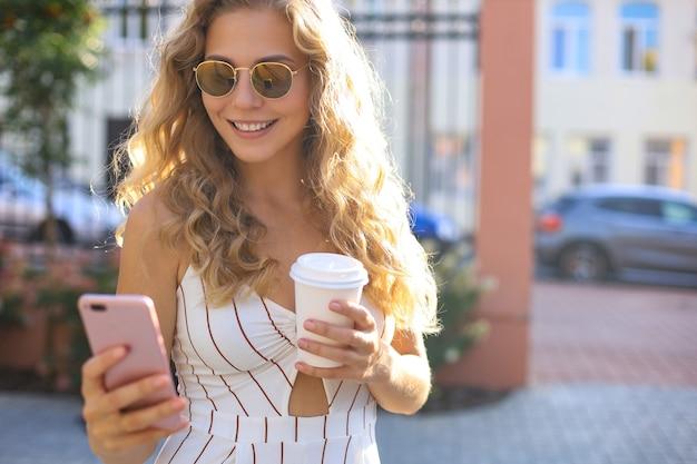 Красивая белокурая женщина обменивается сообщениями на смартфоне на фоне улицы города.
