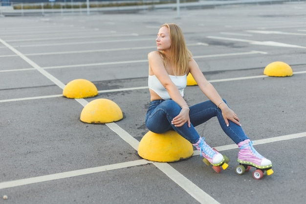 Beautiful blonde woman in jeans in rollers sitting on parking