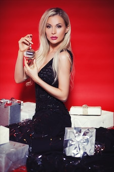 Beautiful blonde woman in long black dress with gift boxes and falling confetti on the red background isolated