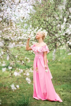 A beautiful blonde woman in a long pink dress walks in a spring blooming garden.