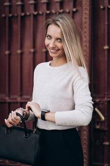 Красивая блондинка смотрит на время на часах, гуляя по улице. портрет стильной улыбающейся деловой женщины в темных повседневных брюках и сливочном свитере. концепция моды. женский деловой стиль.