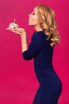 Beautiful blonde woman in luxury blue dress and curly hairstyle blowing candle on birthday cake