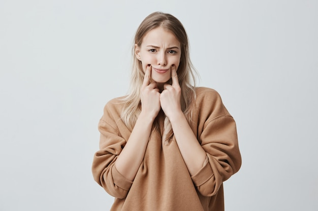 Beautiful blonde woman making grimace, touching her cheeks with fingers, making herself smile, frowning face, being displeased and upset. face expression and negative emotions