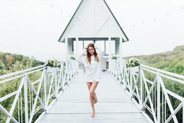 Bella donna bionda in una camicia da uomo sulla terrazza estiva che riposa al resort di lusso. in posa per instagram.