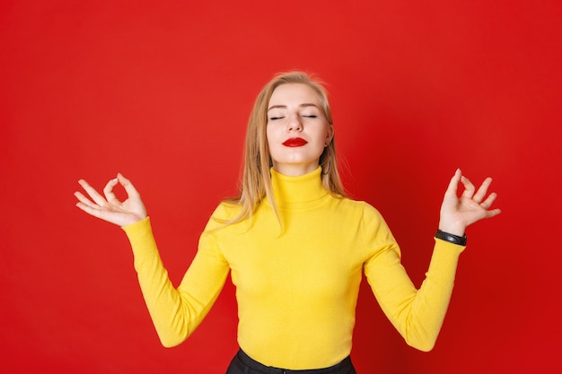Beautiful blonde woman meditating with closed eyes on red background.