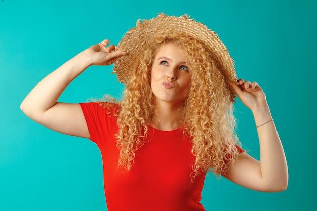 Красивая блондинка модель позирует в соломенной шляпе