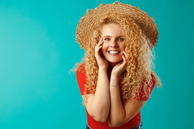 麦わら帽子でポーズをとる美しいブロンドの女性モデル