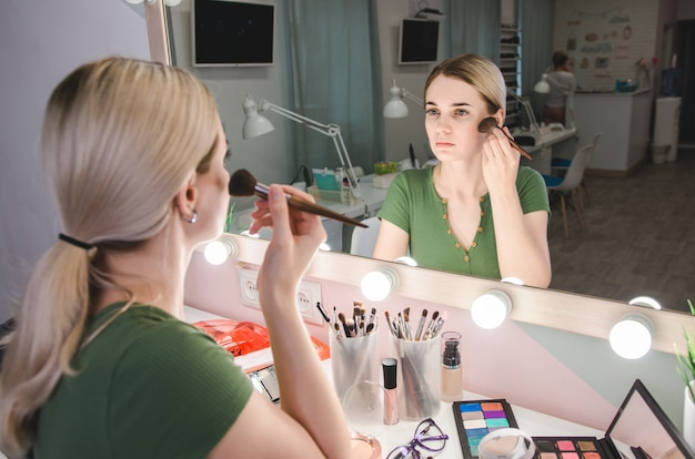 Beautiful blonde woman near mirror in make-up room