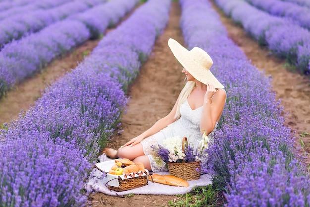 Красивая блондинка на пикнике в сиреневом поле.