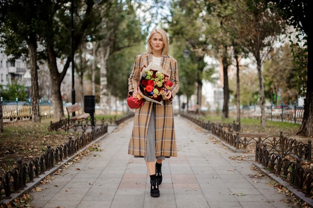 Beautiful blonde woman in plaid coat holding a bright bouquet of flowers standing on alley