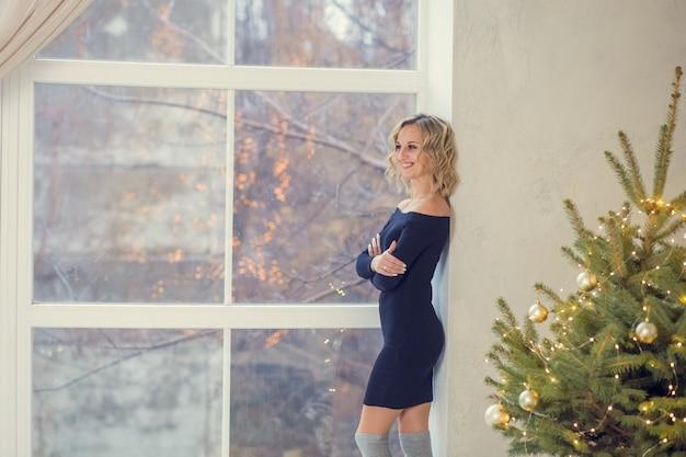 Красивая блондинка позирует возле елки